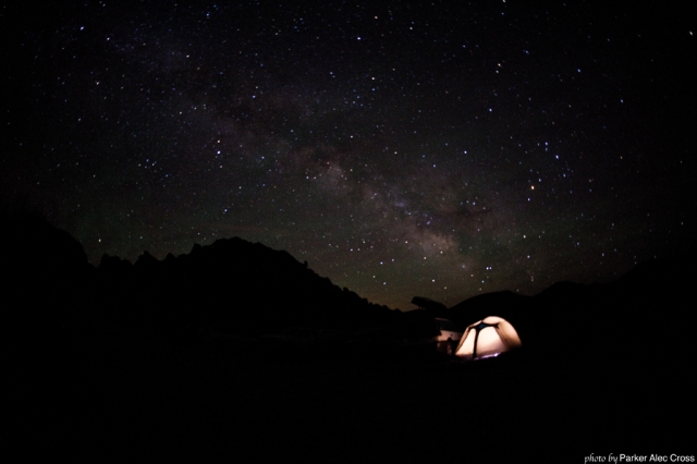 A tent illuminated from within with the stars in the background