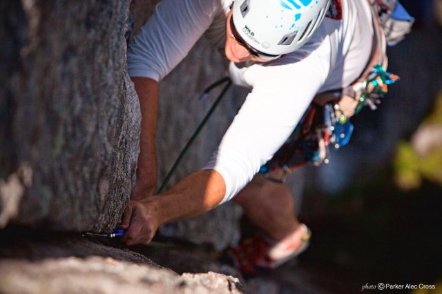 Climber places a small cam into a narrow crack.
